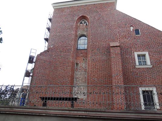 Ściana wschodnia prezbiterium z odkrytym maswerkiem w górnej części zamurowanego okna. Widoczne ślady pierwotnego szczytu  trójkątnego (inny kolor cegły).